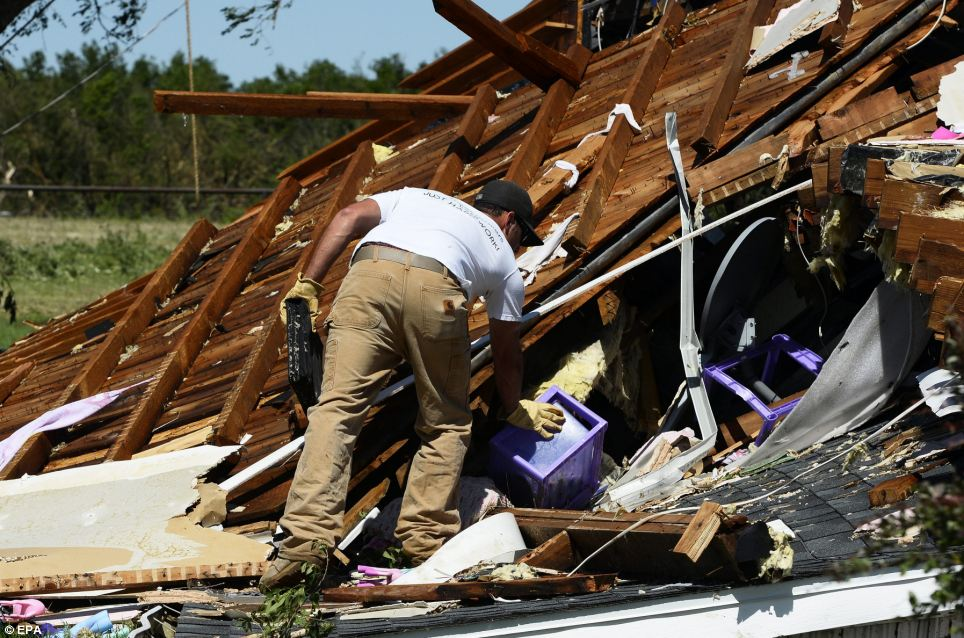 A man looks for items in what is left of a house in El Reno, Oklahoma on Saturday