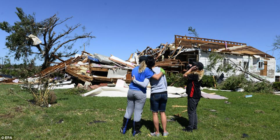 A family in El Reno, Oklahoma inspect what is left of their home after Friday night's tornadoes battered the local area