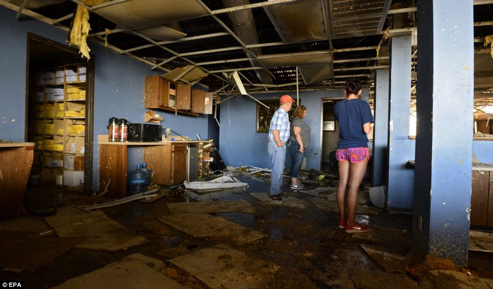 A family inspect the office of what is left of the livestock auction business near El Reno, Oklahoma