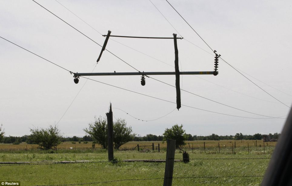 Tornado-damaged power lines hang separated from its pole after tornadoes that swept through central Oklahoma on Friday