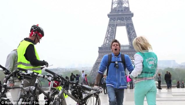 Contagious: Prankster Roman Atwood is seen raucously yawning at a variety of global tourist destinations, including the Eiffel Tower, pictured here