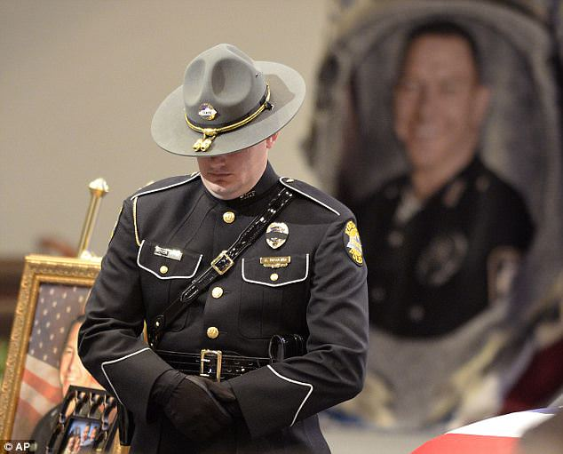 Senseless: Hundreds of officers attended the funeral, including this Kentucky State Trooper, for Ellis who was slayed in a 'senseless act of cowardice'