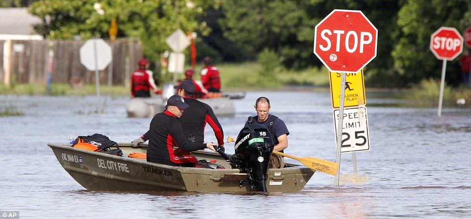 Flooded out: Rescue workers bring residents to dry land. After surviving the tornadoes the region faced flash flooding, with up to 8in of rain falling in 24 hours