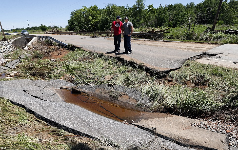 Storm damage: Navy veterans inspect the washed out road where they pulled a woman and her daughter to safety after their car flooded