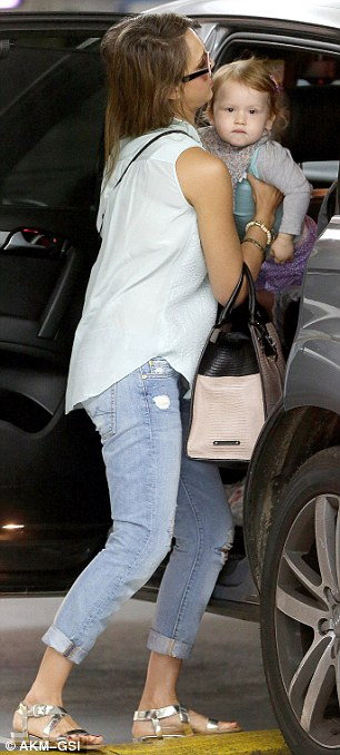 Heavy lifting: The stylish star wore her ombré locks down and was dressed in a pastel green sleeveless top, distressed blue jeans, and silver sandals