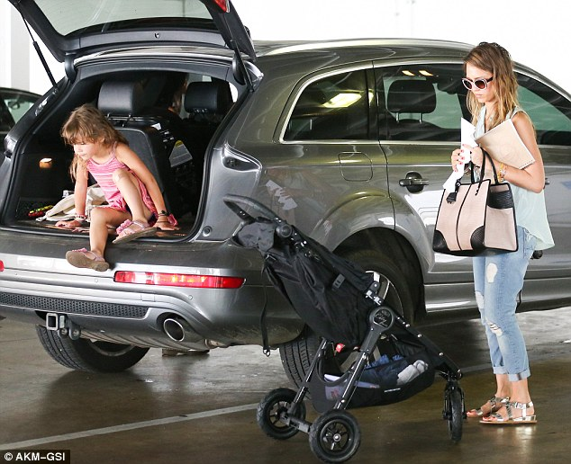I'm coming too!: Four-year-old Honor bizarrely emerged from the boot of the family SUV wearing a pink striped frock and flowered sandals