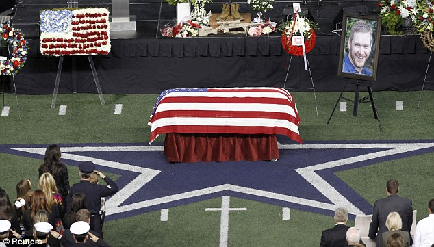 Taya Kyle stands during the playing of Taps during a memorial service for former her husband and Navy SEAL sniper Chris Kyle at Cowboys Stadium in Arlington, Texas, February 11, 2013