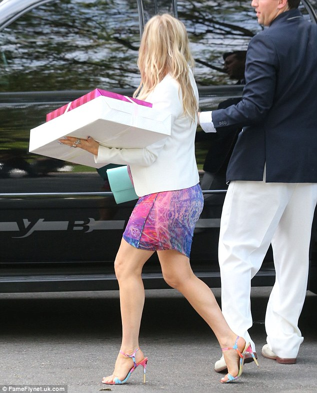 Balancing act: The songstress proceeded to the venue carrying her presents for Heidi in one hand and her designer clutch in the other