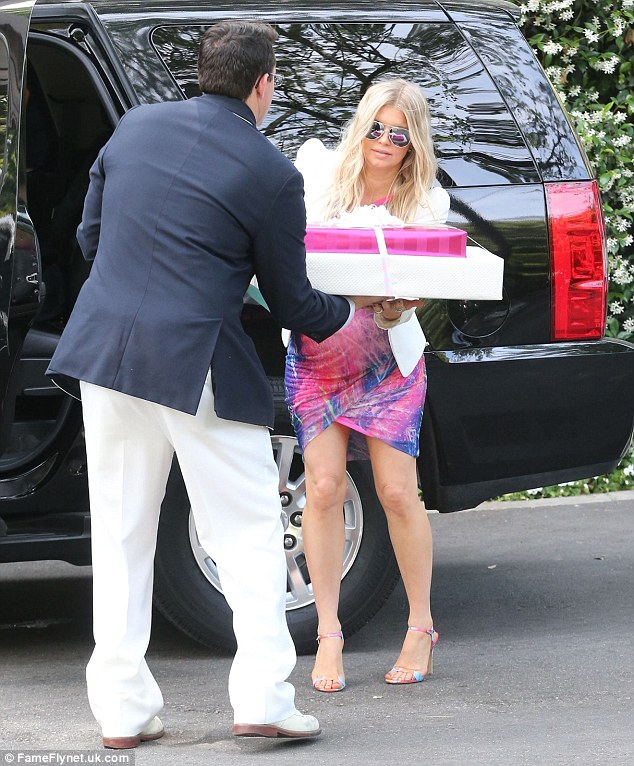 So helpful: Fergie fortunately had help unloading the car of gifts and in that tight dress that was no easy task