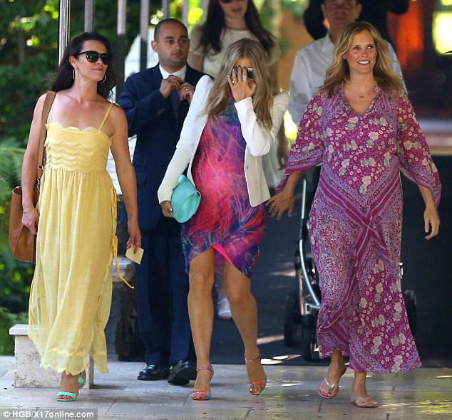 No time for shyness: Fergie pushed her aviator shades with a jeweled hand as she strolled along the hotel walkway with other party guests