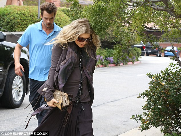 Ducking for cover: Fergie lowered her head beneath a branch while Josh followed close at her heels