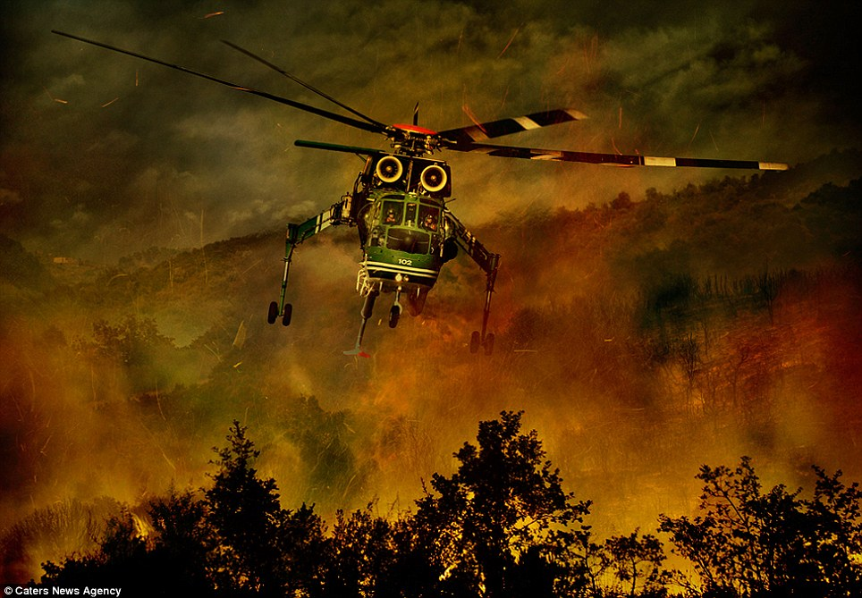 Looming out from the smoke and flames, this helicopter barely clear the trees as its pilots swoop low to tackle the blaze