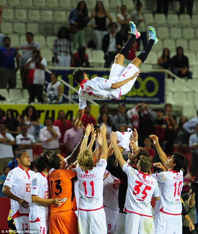 Fond farewell: Navas is thrown in the air by his teammates at the end of Sevilla's last match of the season against Valencia on Saturday