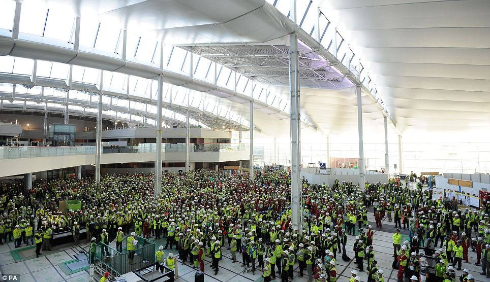Everybody get to work! Workers gather together in the departures hall of Heathrow's Terminal 2 for a talk by Developing Director John Holland-Kaye during an event marking One Year to Go until it re-opens