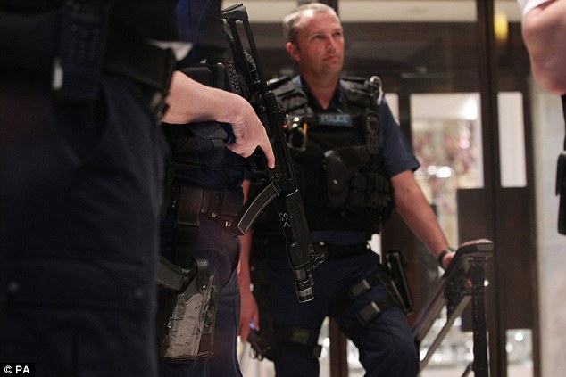 Guns: Police officers at the scene of a smash and grab robbery in Selfridges on Oxford Street in central London