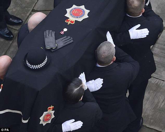 Poignant: The coffin of Fiona Bone, with her hat, gloves and a medal on top, is carried into Manchester Cathedral after processing along the city's Deansgate on Thursday, October last year