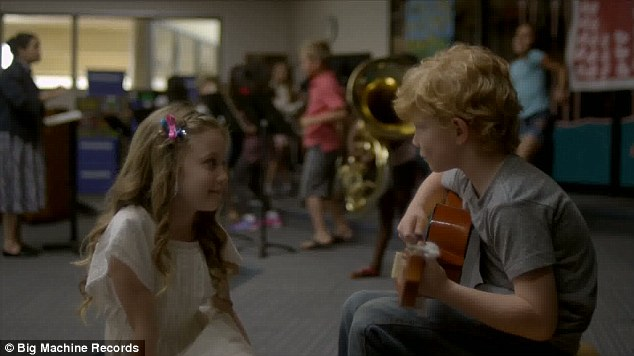 Well that's familiar: The boy played the guitar just like Ed as they sit together in a music lesson as the other children run riot