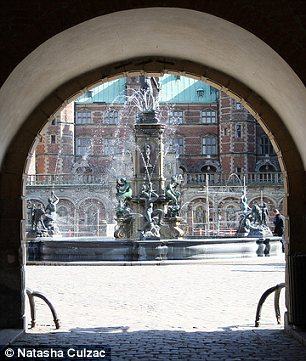 An arch leads to a view of Frederiksborg Castle in the town of Hillerød