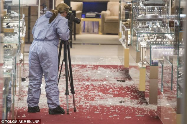 Evidence: A forensic officer photographs the wreckage in Selfridges left after an armed robbery