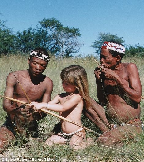 Tippi, aged 6 with Tkui and another man of the San Bushmen of northern Namibia. Tkui is teaching Tippi to use a bow and arrow in Namibia.