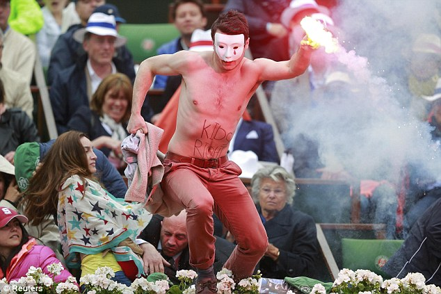 A flare-wielding protester jumps onto the Philippe Chatrier court