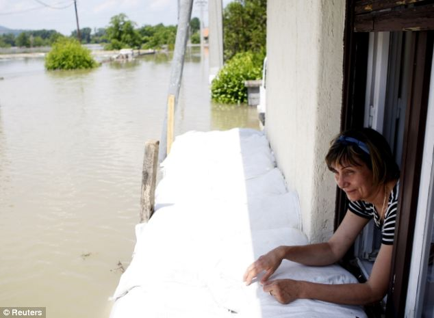A resident looks out from her home 19 miles from Budapest
