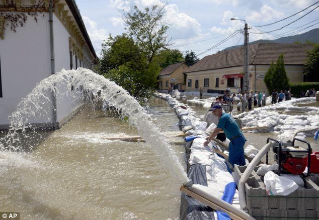 Residents pumping back flood water through a sandbag dam in Nagymaros