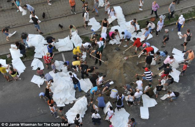 Men, women and children join together to protect their city, making sandbags themselves