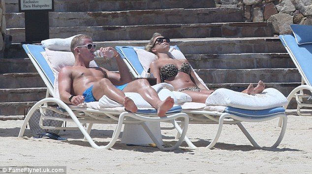 Soaking up the sun: Hart and girlfriend Kimberly lie out in the sun