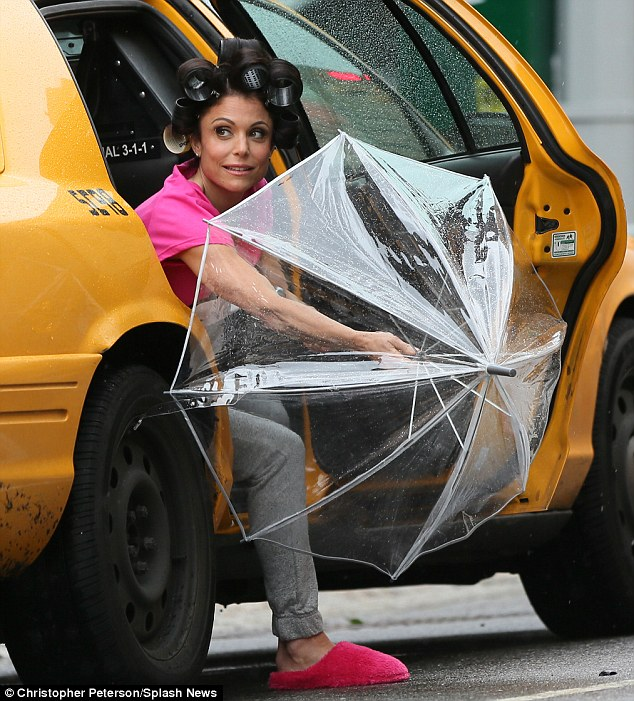 Got to keep dry: The reality star and businesswoman was spotted jumping into a cab in her bizarre ensemble as she took shelter from the inclement weather