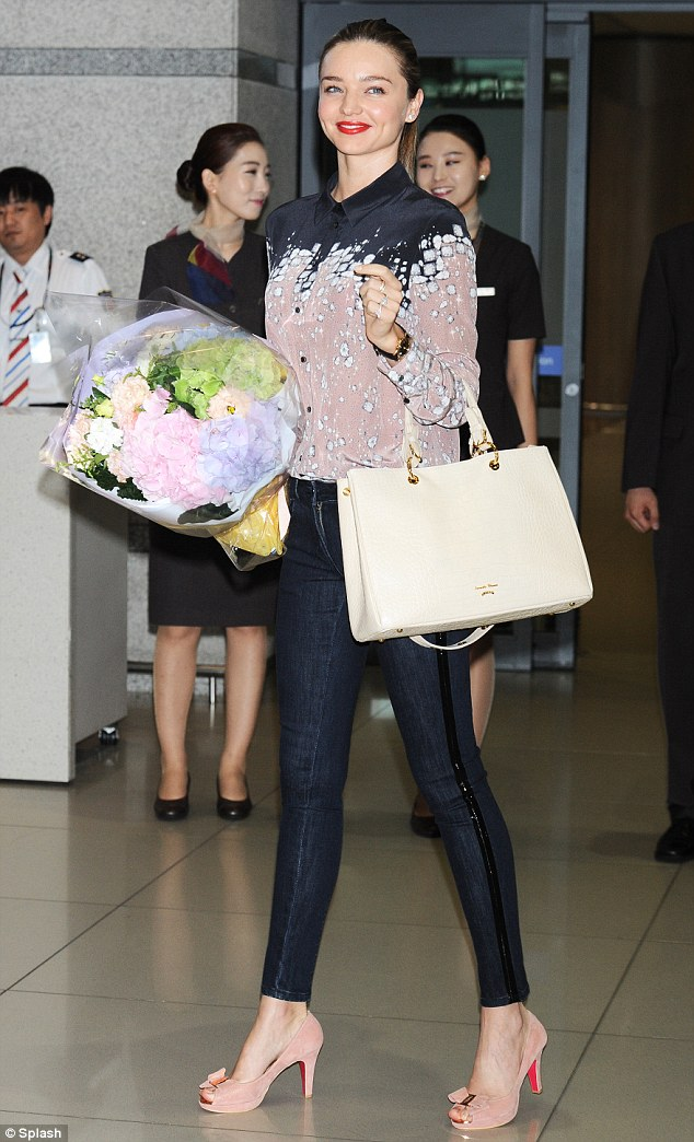 A warm welcome: Miranda looked delighted with a bunch of flowers she had received on arriving in Seoul