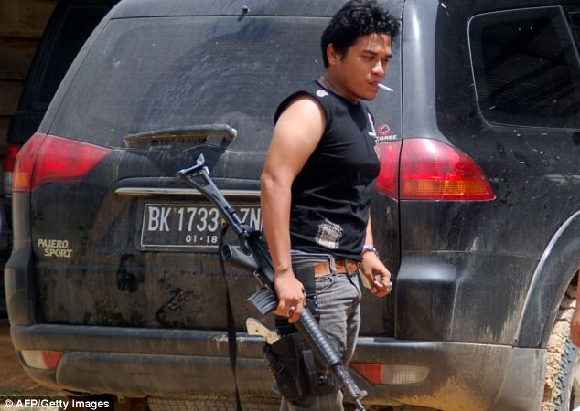 Investigation: An Indonesian policeman walks past a car used by Malcolm Primrose who was kidnapped in Peureulak, East Aceh