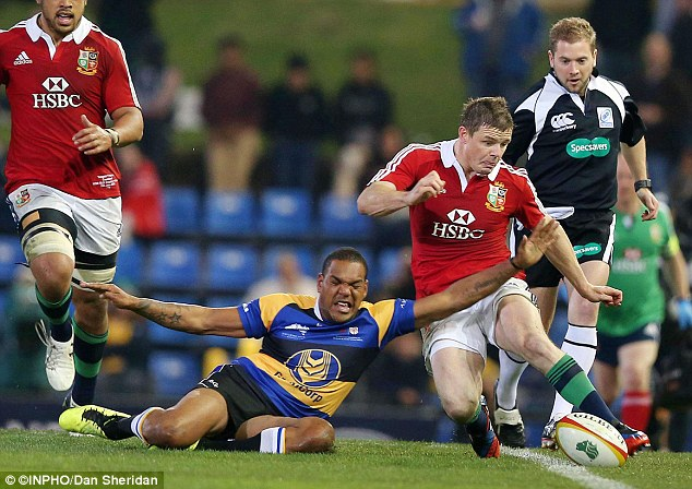 Committed: Brian O'Driscoll attempts a kick against the Combined Country which may have done him damage