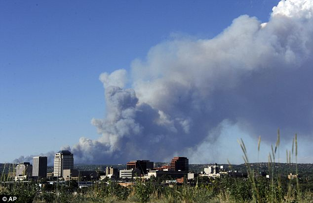 Dangerous: Smoke can be seen over the Colorado Springs skyline as fires rage to the northeast. 38,000 have fled their homes