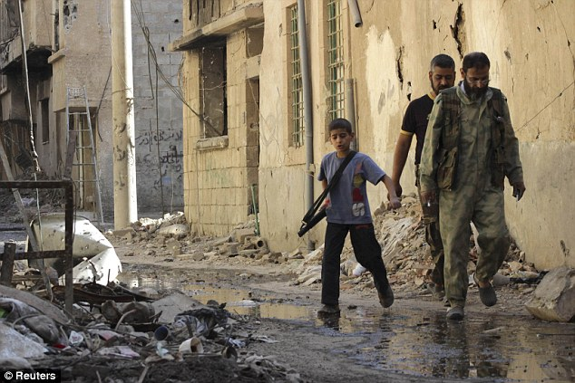 Shocking: A boy carries a weapon as he walks with members of the Free Syrian Army in Deir al-Zor. Among the victims in the conflict were at least 6,561 children, including 1,729 children younger than 10