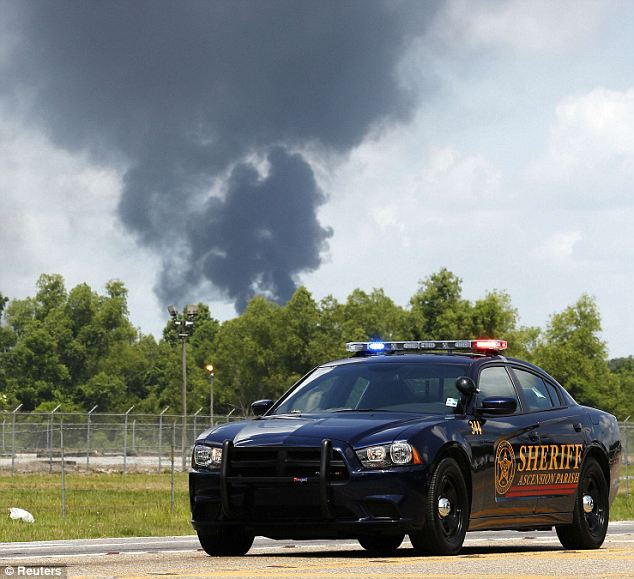 Rushed to the scene: Smoke rises over a local police car. Ascension Parish, Louisiana's Williams-Olefins chemical plant saw a massive explosion Thursday that injured over 30 people