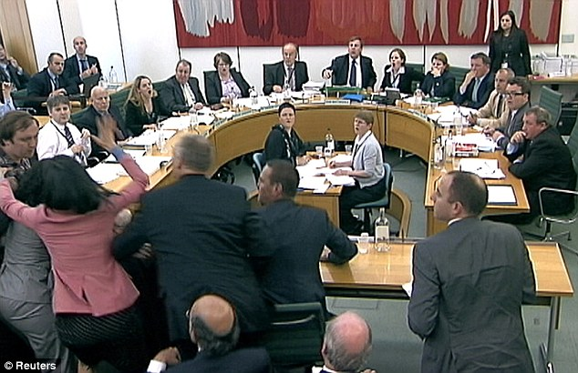 Protection: Wendi Deng lunges towards a man trying to attack her husband during a parliamentary committee hearing on phone hacking on July 19, 2011