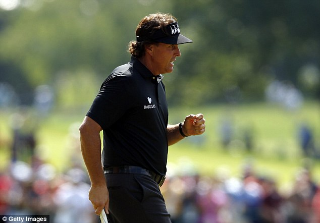 In the hunt: Mickelson pumps his fist after making a birdie putt on the ninth