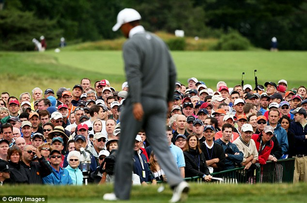 Hot ticket: Tiger Woods walks across the 18th green as a gallery of patrons look on