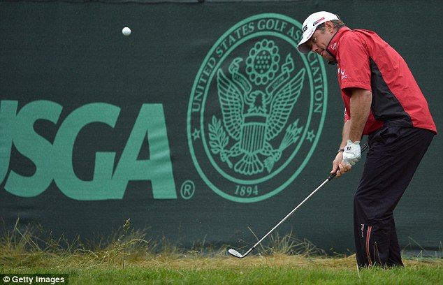 In the red: Lee Westwood chips to the 17th green on Friday morning