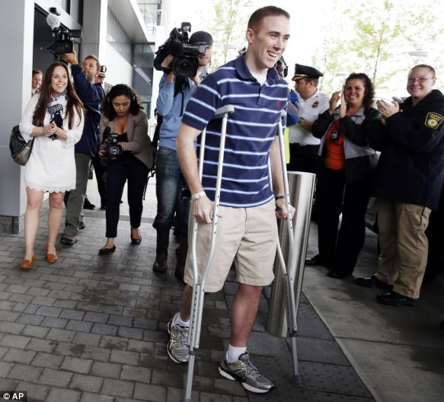 Heading home: Transit police officer Richard Donohue leaves Spaulding Rehabilitation Hospital in Boston followed by his wife Kim, nearly two months after he was shot in the gun battle