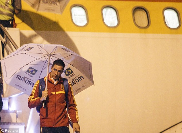 Hiding: Torres uses the umbrella to shelter from the rain as he travels with Spain to the Confederations Cup