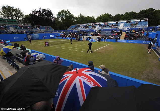 Drizzly: Ground staff prepare to bring on the covers on centre court at the AEGON Classic in Birmingham today