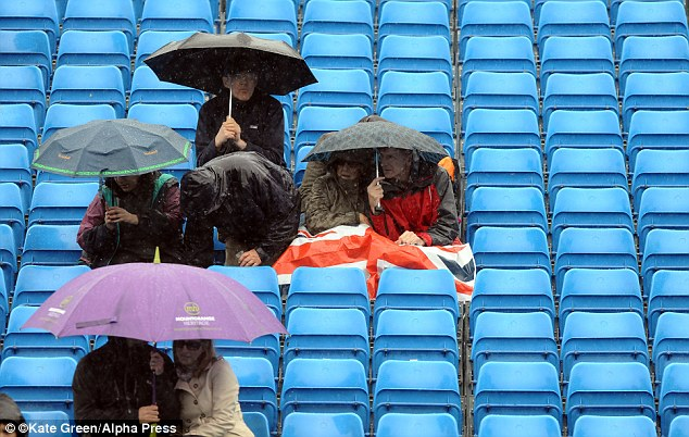 Damp: These brave spectators hold out under umbrellas at the Aegon Championships at the Queens Club London