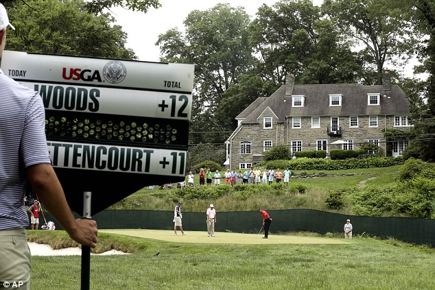 Not quite a full house: Tiger Woods (centre) putts on the 11th hole as Matt Bettencourt looks on