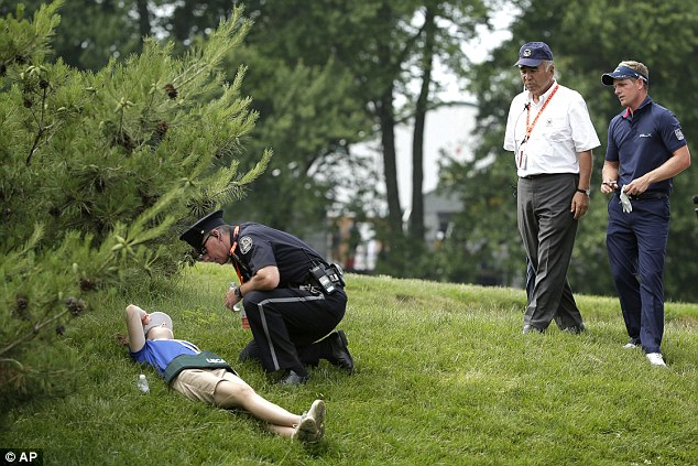 Ouch: Luke Donald (right) watches as a police officer checks on a course worker who was hit by his ball
