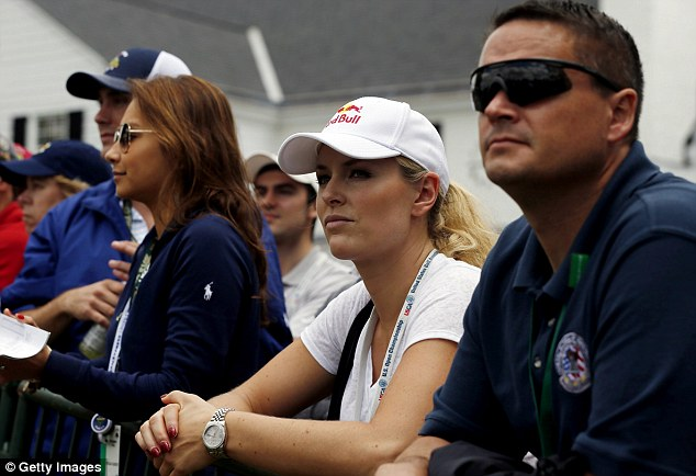 Biggest fan: Vonn waits near the clubhouse as she watches Woods during what has been a rocky performance by the golfer