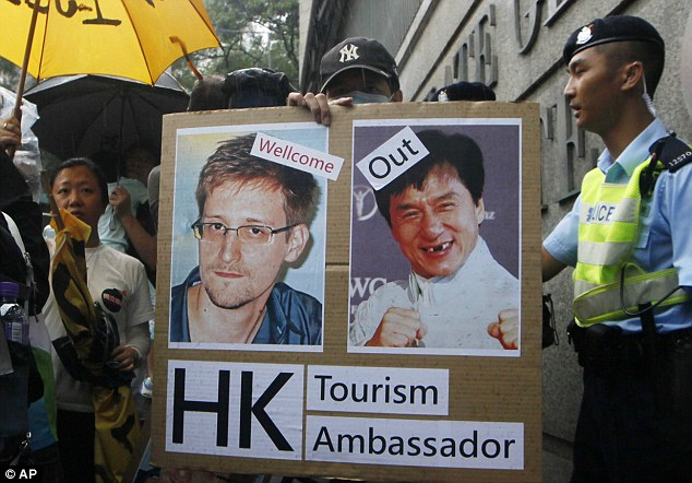 Backing: A supporter holds picture of Snowden and Hong Kong movie star Jackie Chan during a protest outside the Consulate General of the United States in Hong Kong on Saturday