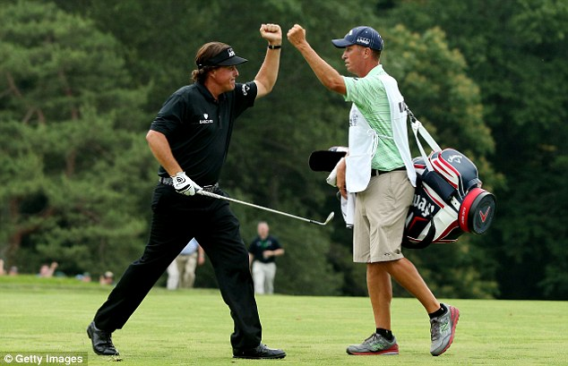 Fist bump: Mickelson celebrates making a shot for eagle on the tenth hole with caddie Jim Mackay