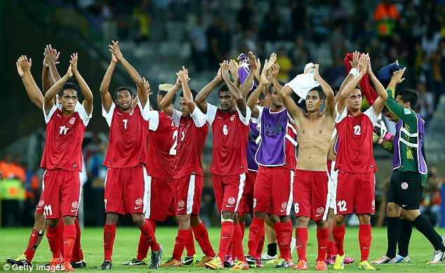 Salute: Tahiti players acknowledge the support of their fans, including the chaps below, after the game